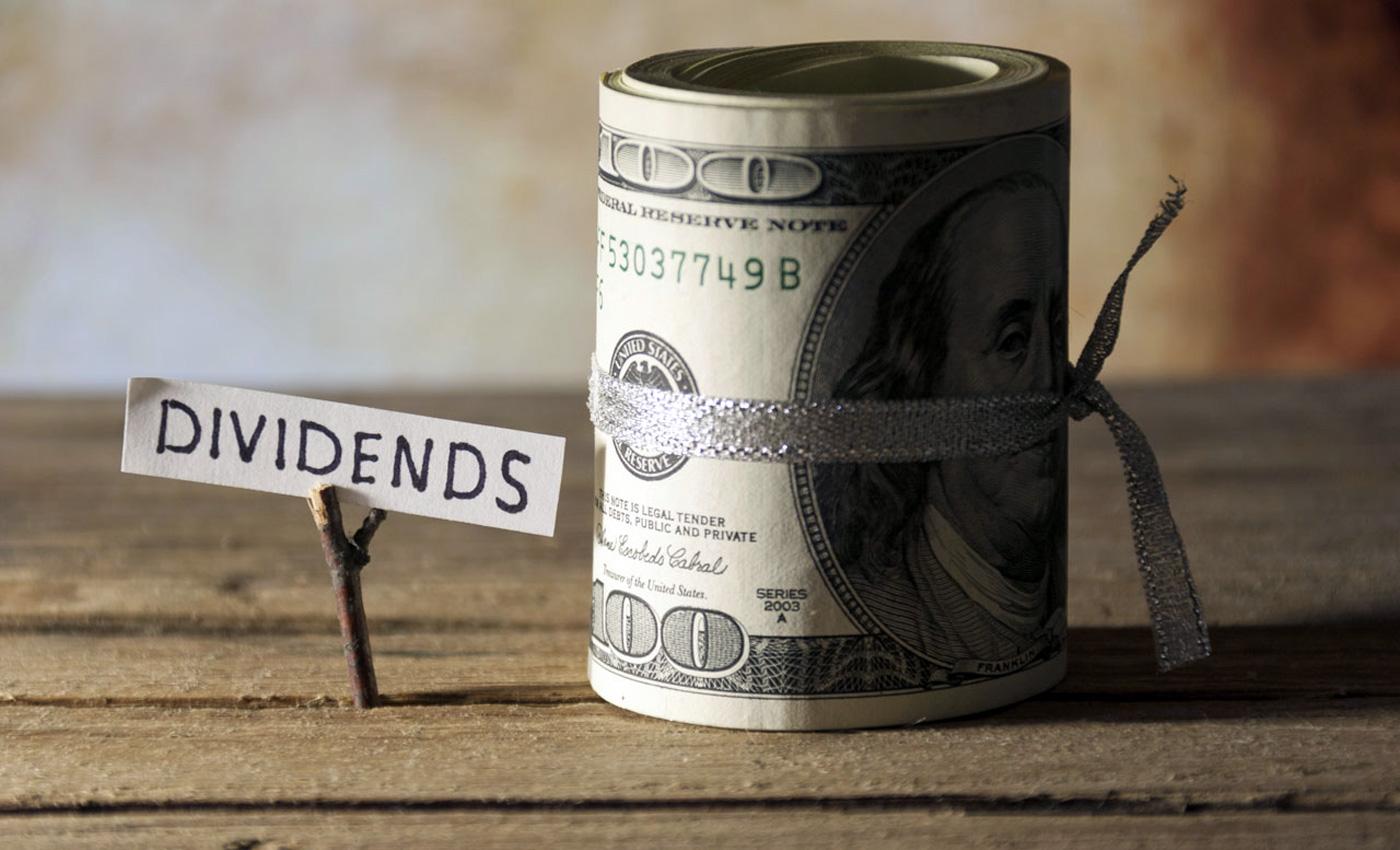 """scritta """"dividendi"""" accanto a banconote arrotolate"""