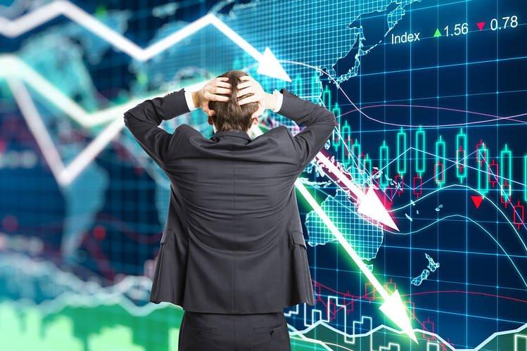 uomo nel panico di fronte ai grafici relativi all'andamento degli investimenti