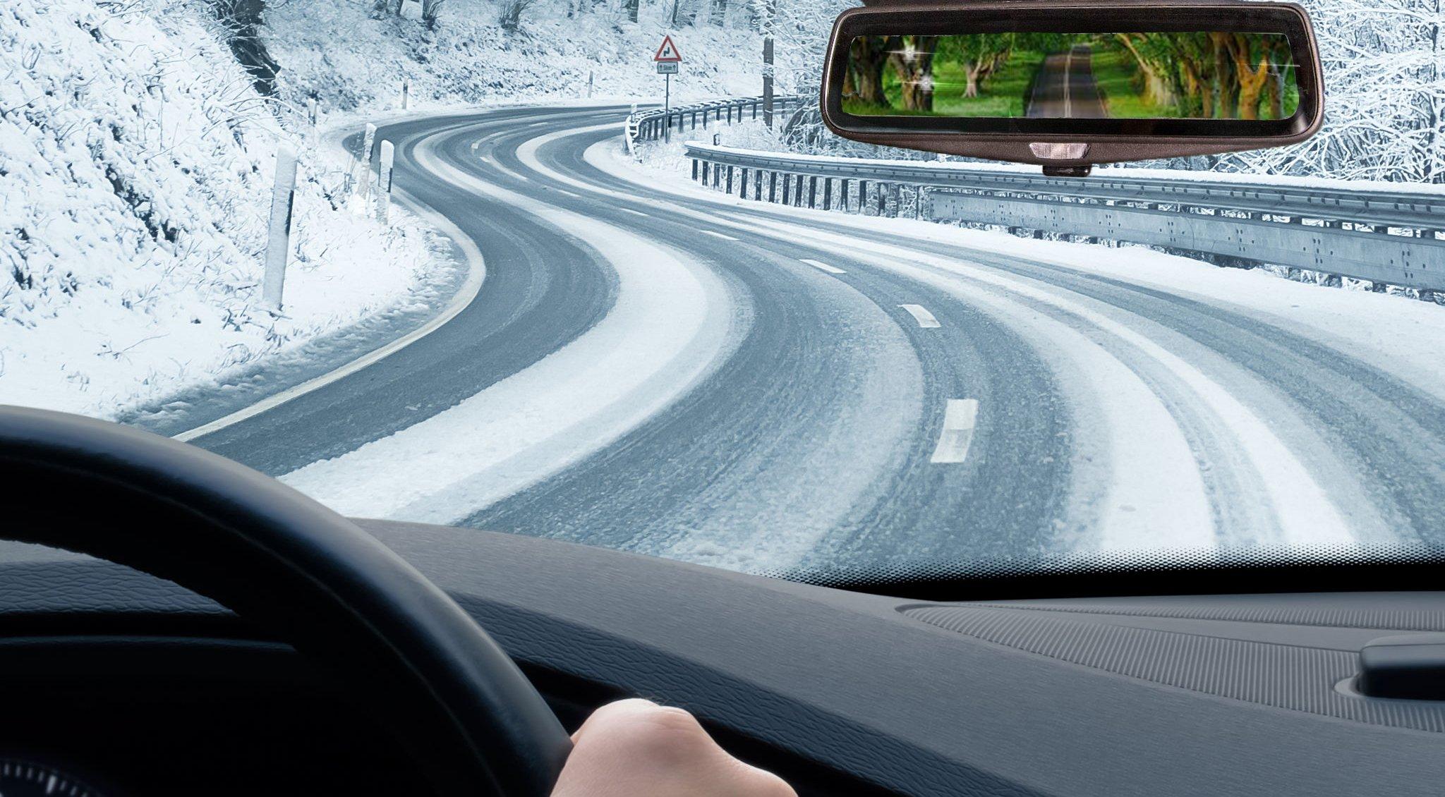 guidare in una strada innevata e guardare in uno specchietto un paesaggio verde